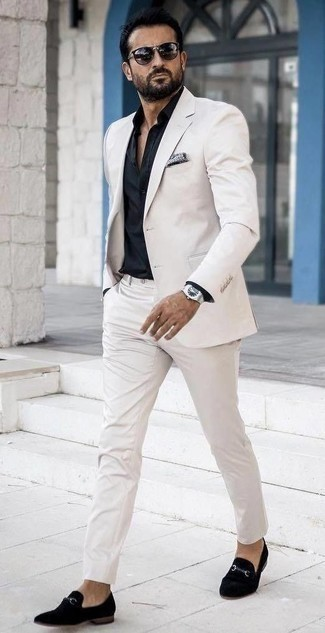 How to Wear a White Suit: You'll be surprised at how super easy it is to throw together this refined getup. Just a white suit and a black dress shirt. Put a more relaxed spin on an otherwise all-too-safe outfit with a pair of black velvet loafers.