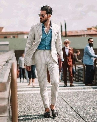 How to Wear a White Suit: You'll be surprised at how easy it is to get dressed like this. Just a white suit worn with a light blue dress shirt. Let your sartorial chops really shine by finishing off this ensemble with a pair of black woven leather loafers.