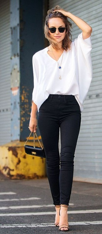 Choose a white long sleeve blouse and black slim jeans for a comfortable outfit that's also put together nicely. Complement this look with khaki leather heeled sandals.