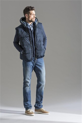 How to Wear a Charcoal Quilted Gilet For Men: Channel your inner cool-kid and consider pairing a charcoal quilted gilet with blue jeans. Let your expert styling really shine by finishing off this getup with tan low top sneakers.