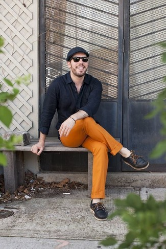 How to wear: black long sleeve shirt, orange chinos, black leather boat shoes, black flat cap