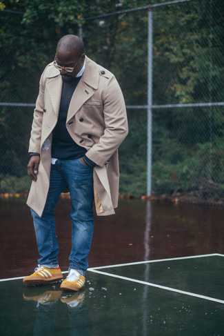 How to Wear Yellow Low Top Sneakers For Men: You'll be amazed at how super easy it is for any gent to pull together this classic and casual outfit. Just a beige trenchcoat and blue jeans. And if you need to immediately tone down this look with footwear, why not add a pair of yellow low top sneakers to the mix?