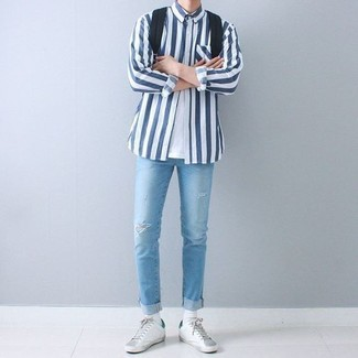 How to wear: white and navy vertical striped long sleeve shirt, white crew-neck t-shirt, light blue ripped skinny jeans, white leather low top sneakers