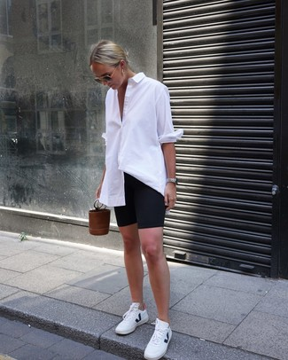 How to wear: brown leather bucket bag, white leather low top sneakers, black bike shorts, white dress shirt