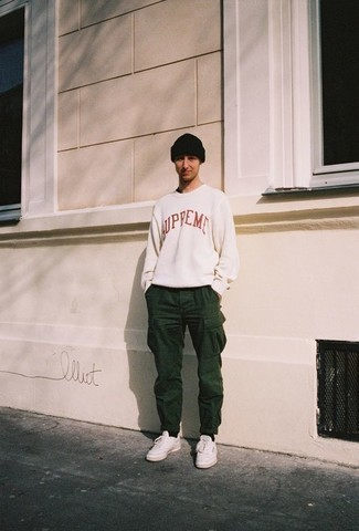 How to Wear White Leather Low Top Sneakers For Men: This combination of a white and red print sweatshirt and dark green cargo pants is a safe bet for an effortlessly cool outfit. A pair of white leather low top sneakers makes this look whole.