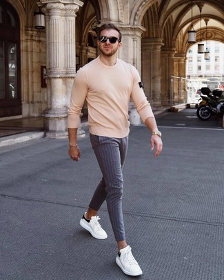 How to wear: black sunglasses, white and black leather low top sneakers, grey vertical striped chinos, beige crew-neck sweater