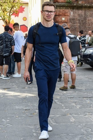 How to Wear a Black Backpack For Men: This combination of a navy crew-neck t-shirt and a black backpack is a safe go-to for an effortlessly dapper outfit. Amp up the classiness of your outfit a bit with a pair of white low top sneakers.