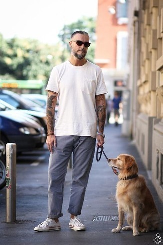 How to Wear White Canvas Low Top Sneakers For Men: To assemble a casual getup with a twist, reach for a white crew-neck t-shirt and blue chinos. Complement this look with white canvas low top sneakers and the whole outfit will come together.
