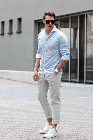 How to wear: black sunglasses, white leather low top sneakers, grey chinos, light blue vertical striped long sleeve shirt