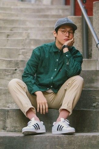 How to wear: grey baseball cap, white and black horizontal striped leather low top sneakers, beige chinos, dark green vertical striped long sleeve shirt