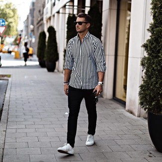 How to wear: black sunglasses, white leather low top sneakers, black chinos, white and black vertical striped long sleeve shirt