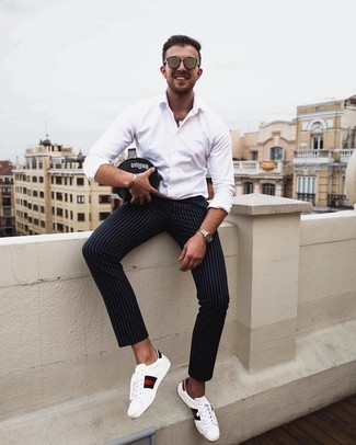 How to wear: brown sunglasses, white print leather low top sneakers, black vertical striped chinos, white long sleeve shirt