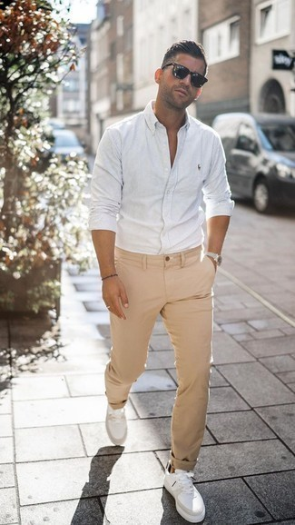 How to Wear Khaki Chinos: If you're looking to take your off-duty style game up a notch, marry a white vertical striped long sleeve shirt with khaki chinos. A nice pair of white leather low top sneakers ties this look together.