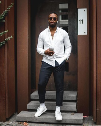 How to Wear a Silver Watch For Men: If you're a jeans-and-a-tee kind of guy, you'll like this basic yet casually dapper combination of a white long sleeve shirt and a silver watch. Ramp up the classiness of this look a bit by finishing off with white leather low top sneakers.
