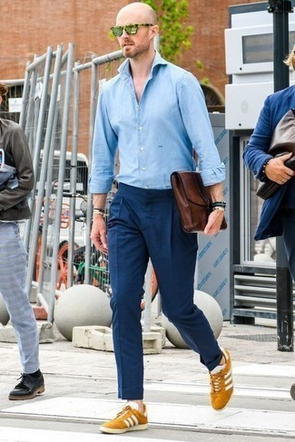 How to Wear a Brown Leather Zip Pouch For Men: Flaunt your prowess in menswear styling by putting together a light blue chambray long sleeve shirt and a brown leather zip pouch for an edgy outfit. Feeling brave? Spruce up your look by slipping into a pair of tobacco suede low top sneakers.