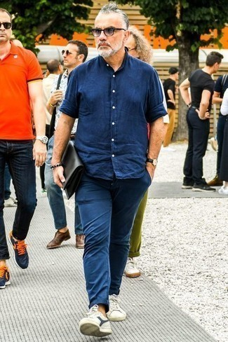 How to Wear a Navy Chambray Long Sleeve Shirt For Men: Go for a pared down but at the same time neat and relaxed choice marrying a navy chambray long sleeve shirt and navy chinos. And if you wish to instantly dress down this outfit with one single piece, complement this outfit with white and navy canvas low top sneakers.