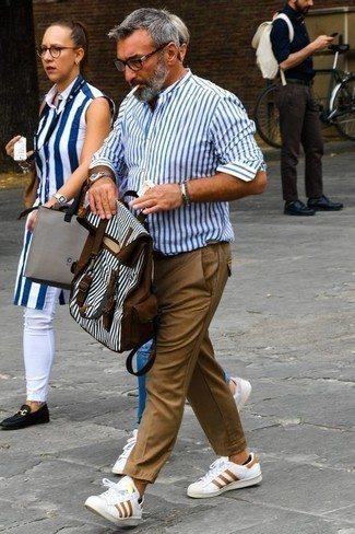 How to Wear Khaki Chinos: A white and blue vertical striped long sleeve shirt and khaki chinos? This is an easy-to-style ensemble that any man could rock on a daily basis. Slip into a pair of white print leather low top sneakers and the whole look will come together.