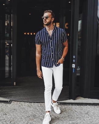 How to wear: black sunglasses, white leather low top sneakers, white chinos, navy and white vertical striped short sleeve shirt