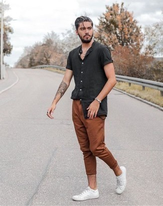 How to Wear White Canvas Low Top Sneakers For Men: This outfit with a charcoal short sleeve shirt and tobacco chinos isn't so hard to create and leaves room to more sartorial experimentation. White canvas low top sneakers are a welcome complement for this ensemble.