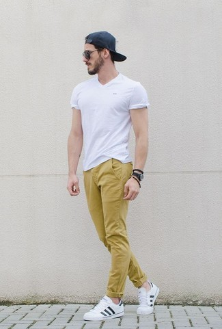 How to wear: black baseball cap, white leather low top sneakers, mustard chinos, white v-neck t-shirt