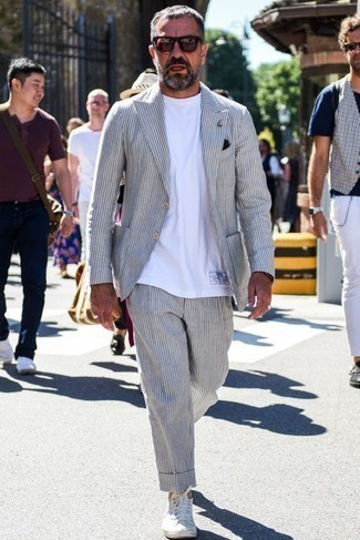 Men's Looks & Outfits: What To Wear In 2020: This combination of a grey vertical striped suit and a white crew-neck t-shirt is a must-try casually smart outfit for any modern gentleman. A pair of white canvas low top sneakers will contrast beautifully against the rest of the look.