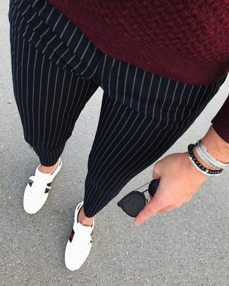 How to wear: black sunglasses, white leather low top sneakers, black vertical striped dress pants, burgundy crew-neck sweater
