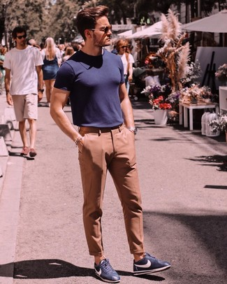 How to wear: dark brown sunglasses, navy leather low top sneakers, khaki dress pants, navy crew-neck t-shirt