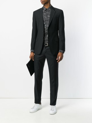 How to Wear a Black Suit: This is definitive proof that a black suit and a black and white polka dot dress shirt look amazing when combined together in a classy look for a modern gentleman. Go ahead and complement your look with white leather low top sneakers for a more relaxed feel.