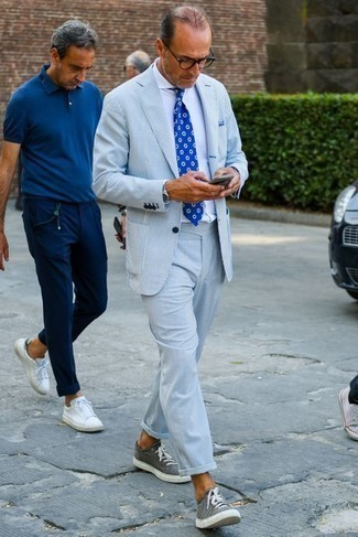 How to Wear a White Dress Shirt For Men: Marrying a white dress shirt and a light blue vertical striped suit is a guaranteed way to infuse your styling lineup with some rugged sophistication. Add grey canvas low top sneakers to your ensemble to inject a sense of stylish casualness into this outfit.