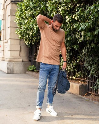 How to wear: navy canvas backpack, white leather low top sneakers, blue jeans, tan crew-neck t-shirt
