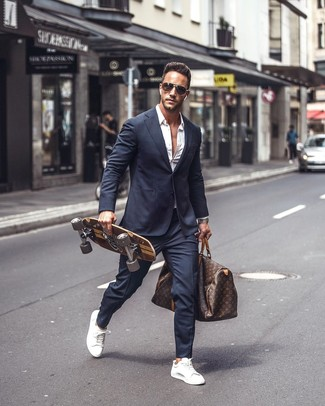 How to wear: dark brown print leather holdall, white leather low top sneakers, white long sleeve shirt, navy suit