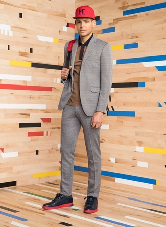 How to wear: red canvas backpack, black leather low top sneakers, brown polo, grey wool suit