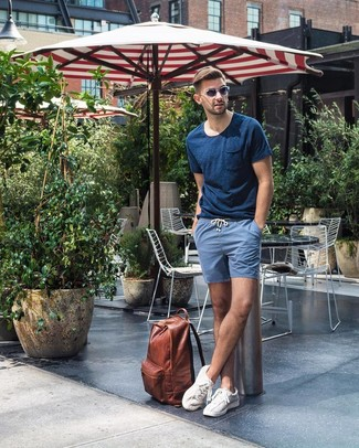 How to wear: brown leather backpack, white low top sneakers, blue shorts, navy crew-neck t-shirt