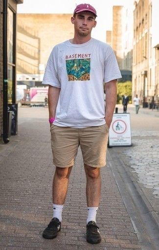 How to Wear Tan Shorts For Men: A white print crew-neck t-shirt and tan shorts are an easy way to introduce extra cool into your daily styling routine. On the shoe front, this look pairs nicely with black canvas low top sneakers.