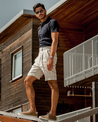 How to wear: dark brown sunglasses, brown suede low top sneakers, grey linen shorts, navy polo