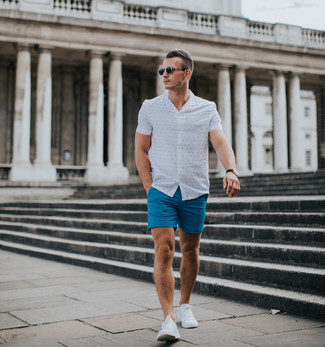 How to wear: black sunglasses, white low top sneakers, blue shorts, white print short sleeve shirt