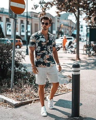 How to Wear White Canvas Low Top Sneakers For Men: This laid-back pairing of a navy floral short sleeve shirt and white shorts is perfect if you need to feel confident in your getup. Introduce a pair of white canvas low top sneakers to the mix and you're all done and looking awesome.