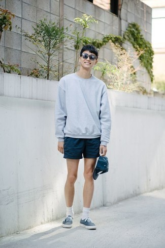 How to Wear Navy Canvas Low Top Sneakers For Men: This combo of a light blue sweatshirt and navy shorts is a safe go-to for a truly dapper ensemble. A pair of navy canvas low top sneakers makes your getup whole.