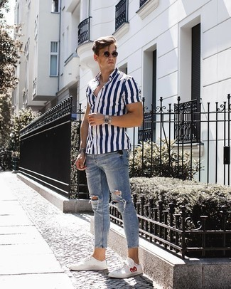 Men's Looks & Outfits: What To Wear In 2020: For a laid-back ensemble, try pairing a navy and white vertical striped short sleeve shirt with light blue ripped skinny jeans — these items go perfectly well together. To give this outfit a classier finish, why not complement this outfit with a pair of white print low top sneakers?