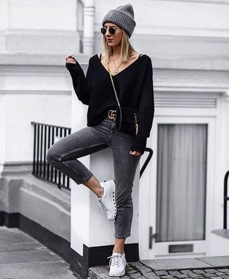 How to wear: black suede crossbody bag, white low top sneakers, charcoal skinny jeans, black v-neck sweater