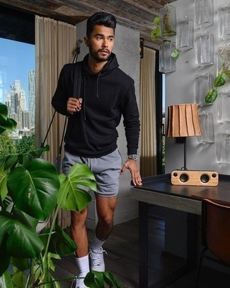 How to Wear a Black Hoodie For Men: We all look for comfort when it comes to styling, and this casual street style combination of a black hoodie and light blue sports shorts is a perfect example of that. Add a more polished twist to an otherwise simple ensemble by rocking a pair of white canvas low top sneakers.