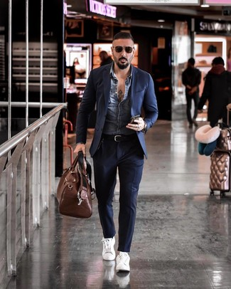 How to wear: brown leather holdall, white leather low top sneakers, navy suit, blue denim jacket