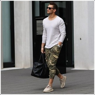 How to wear: black leather holdall, beige low top sneakers, olive camouflage sweatpants, white crew-neck sweater