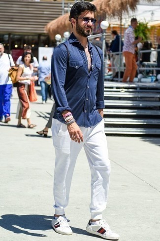 How to Wear White Print Leather Low Top Sneakers For Men: This casual combo of a navy long sleeve shirt and white sweatpants is a winning option when you need to look laid-back and cool in a flash. A pair of white print leather low top sneakers is a savvy pick to finish your ensemble.