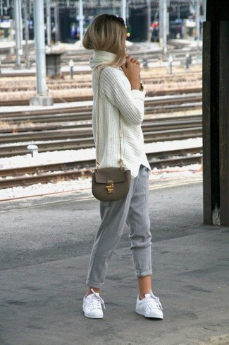 How to wear: olive leather crossbody bag, white low top sneakers, grey tapered pants, white knit oversized sweater