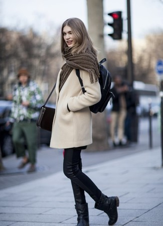 How to wear: black leather backpack, black leather mid-calf boots, black leather skinny jeans, beige coat