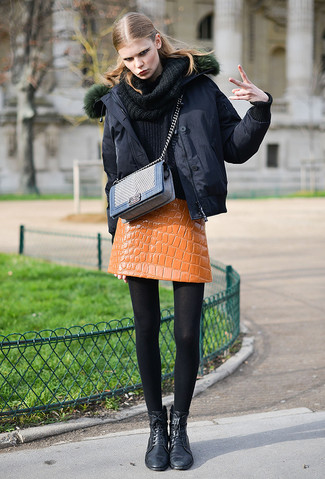 How to wear: black leather lace-up flat boots, orange leather mini skirt, black cowl-neck sweater, black puffer jacket