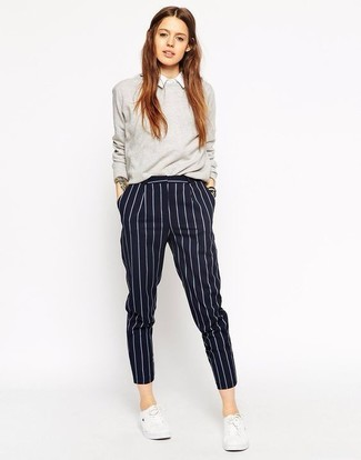 How to Wear Navy Vertical Striped Dress Pants For Women: Stylish yet comfy, this getup is comprised of a grey crew-neck sweater and navy vertical striped dress pants. Tone down your ensemble by rounding off with a pair of white low top sneakers.