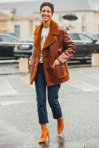 How to wear: tobacco leather ankle boots, navy jeans, white and black print crew-neck t-shirt, tobacco shearling jacket