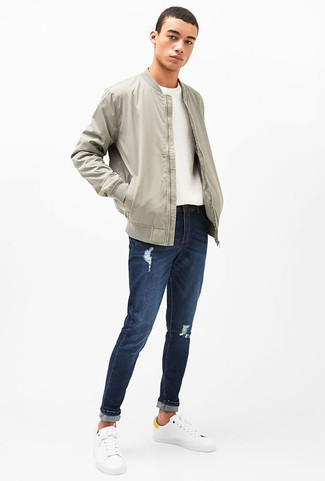 How to wear: white leather low top sneakers, navy ripped jeans, white crew-neck sweater, grey bomber jacket